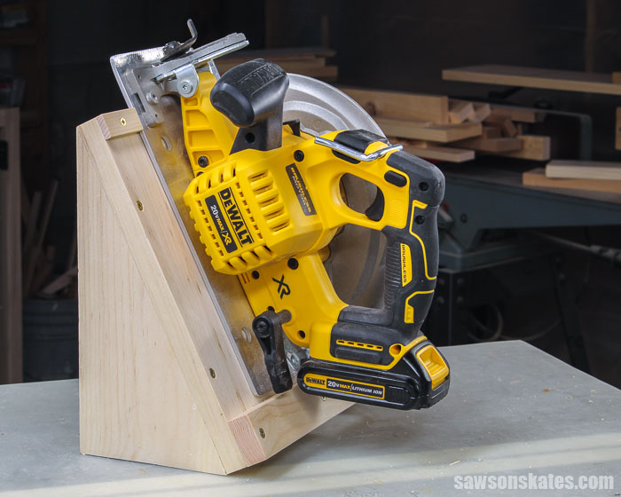 Left side of a DIY circular saw storage holder with a DeWalt saw on a workbench