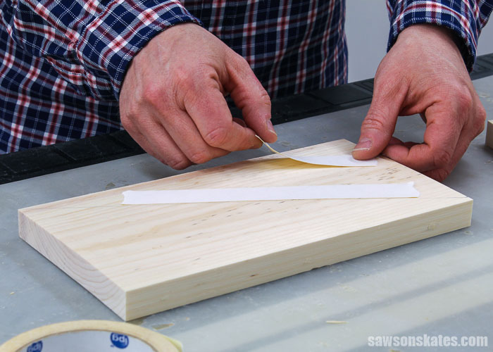 Hands applying double-sided tape to the side of a DIY circular saw storage rack