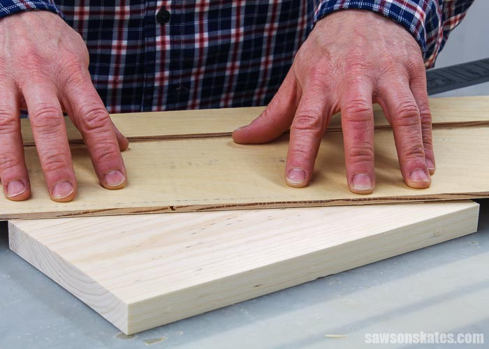 Hands pressing a crosscut jig on the side of a DIY circular saw rack