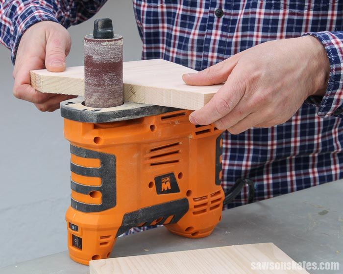 Using a spindle sander to smooth the edges of a DIY 3 tiered spice rack