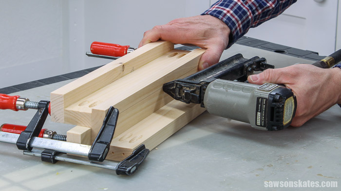 Using a nail gun to attach the middle shelf to the bottom shelf of a DIY tiered spice rack