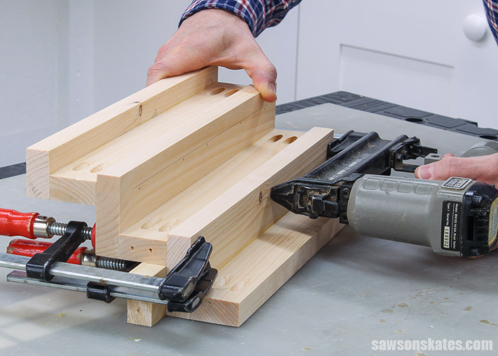 Using a nail gun to attach the top shelf to the middle shelf of a DIY tiered spice rack