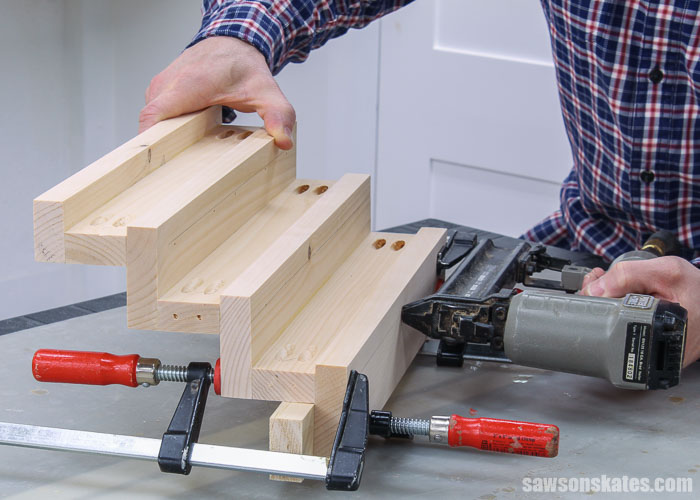 Using a nail gun to attach the back to the top shelf of a DIY tiered spice rack