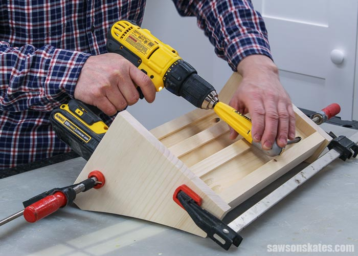 Using a drill to attach the shelves to the sides of a DIY 3 tier spice rack