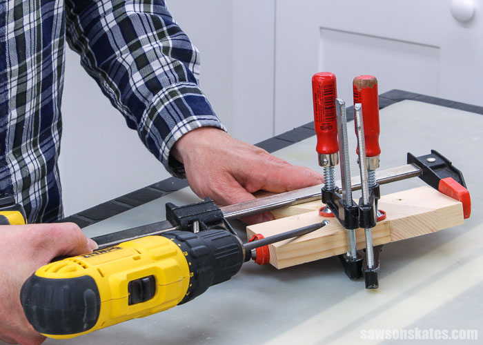 Driving a screw in the bottom holder of a DIY saw blade holder