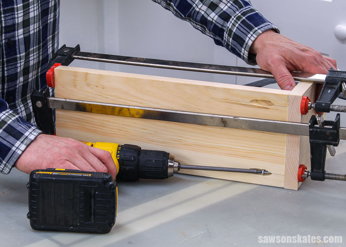 Using a drill to attach the back of a DIY saw blade storage rack