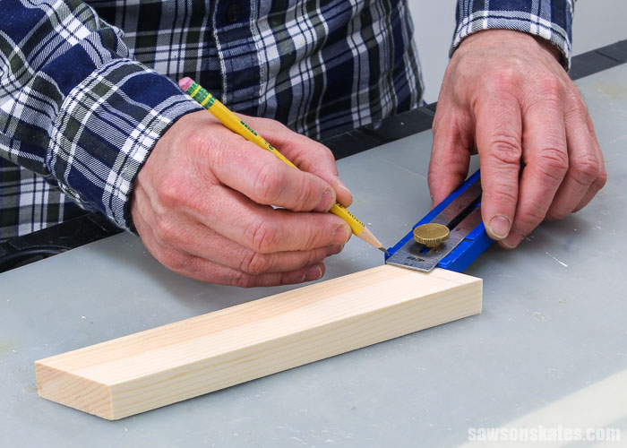 Using a pencil to mark the holders of a DIY saw blade storage rack