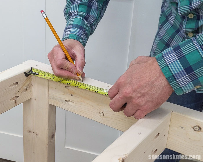 Using a pencil to mark the locations for fasteners to attach the top on a DIY tool stand
