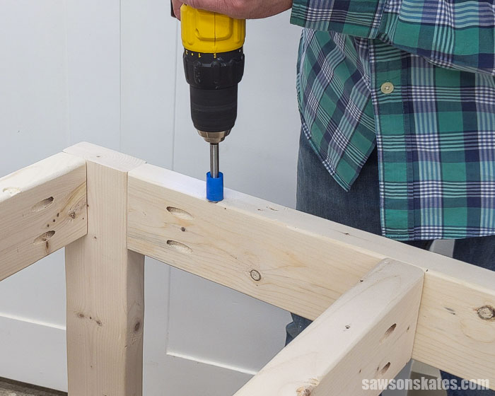 Using a drill to make holes for fasteners to attach the top on a small DIY tool stand