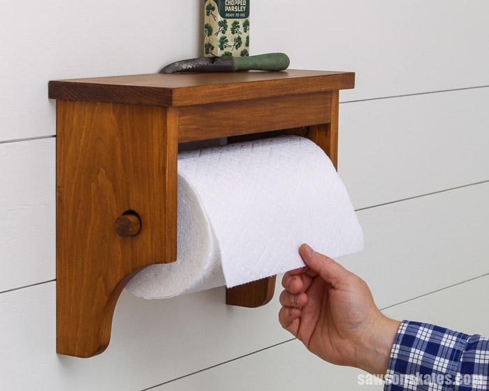 Make this simple DIY wall-mounted paper towel holder with storage shelf and curved details.