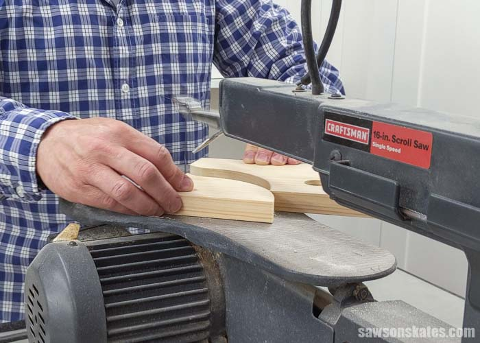 Using a scroll saw to cut the side of a wall-mounted DIY paper towel holder