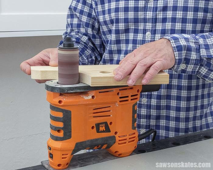 Using a spindle sander to smooth the edges of a DIY paper towel holder