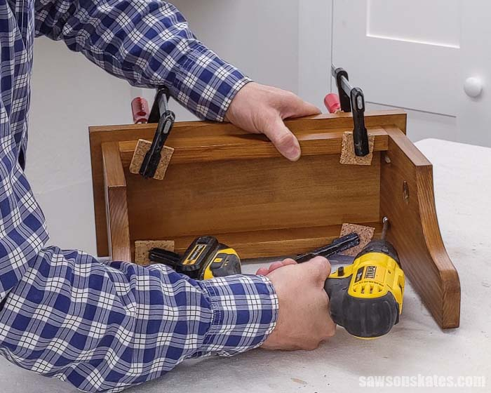 Attaching the shelf to handmade wall-mounted paper towel holder.