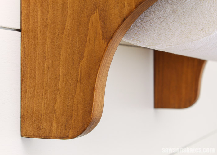 Curved detail at the bottom of a handmade wall-mounted paper towel holder