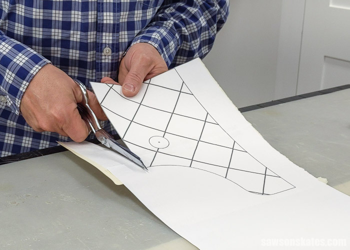 Scissors cutting out the template for a handmade wall-mounted paper towel holder