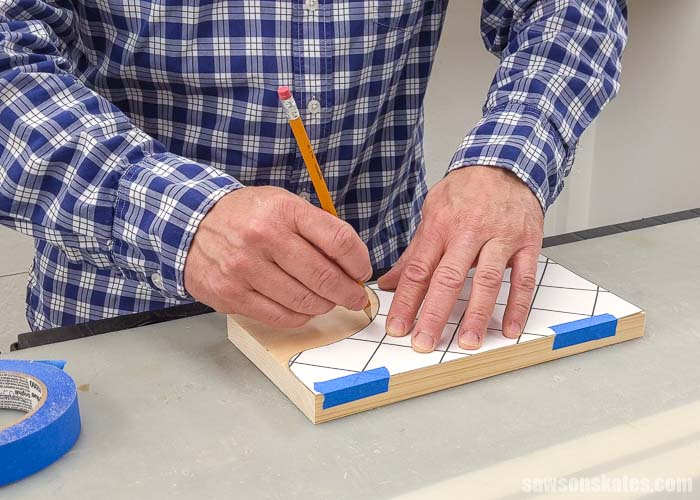 Using a pencil to trace the template for a wall-mounted paper towel holder