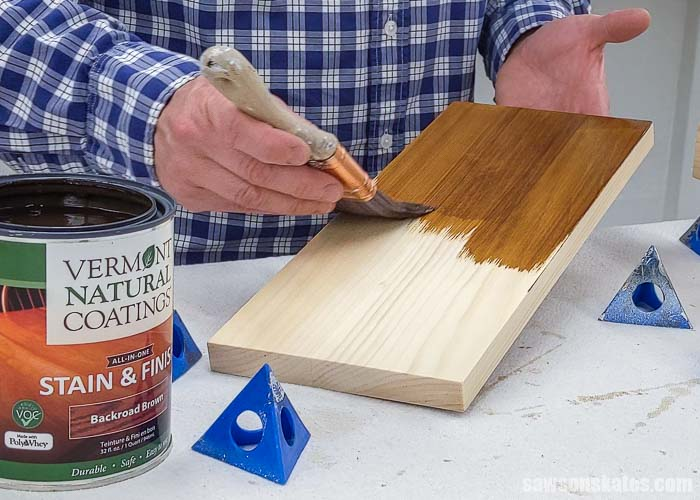 Using a brush to apply a stain and poly in one to the backside of a board