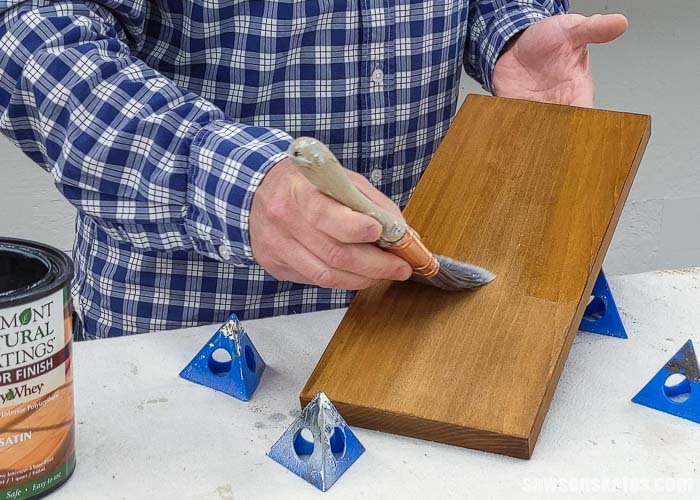 Applying a top coat to the backside of a board after applying a stain and polyurethane in one