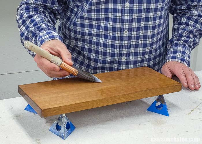 Applying a top coat to the front side of a board after applying a stain and polyurethane in one