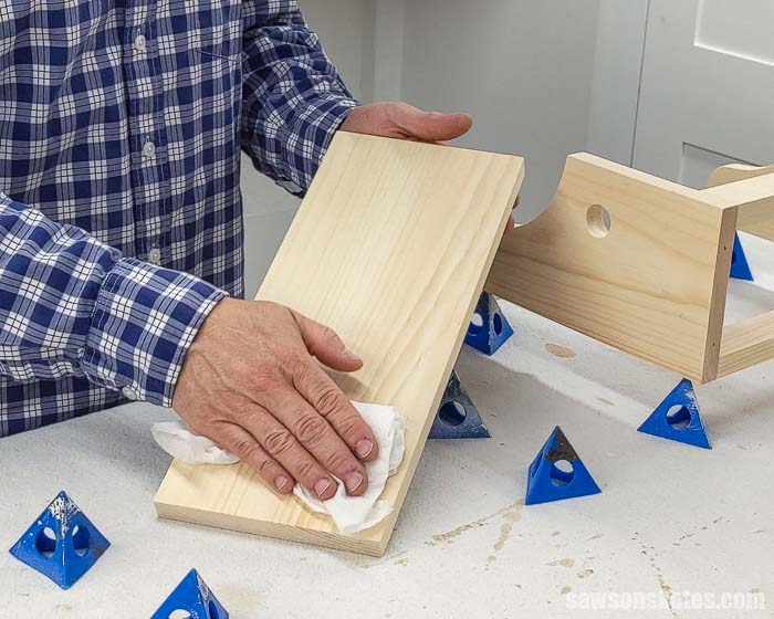 Using a damp rag to remove sanding dust before applying a stain and polyurethane in one
