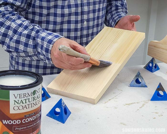 Using a brush to apply wood conditioner to the backside of a board before applying a stain and polyurethane in one
