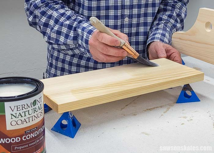 Using a brush to apply wood conditioner to the front side of a board before applying a stain and polyurethane in one