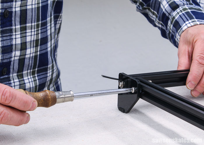 Using a screwdriver to attach the front foot of an Ortur Laser Master 2