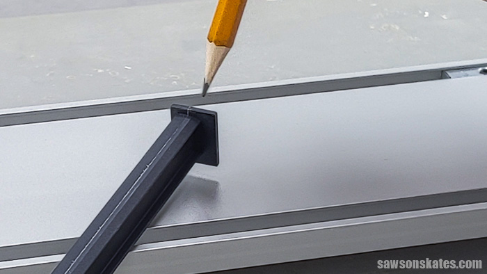 Pencil pointing to the wider edge of the   cutline indicator arm on a Kreg Straight Edge Guide
