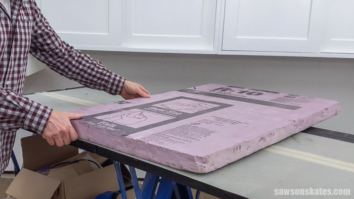 Placing a piece of rigid foam insulation on a workbench before making a cut with Kreg Straight Edge Guide