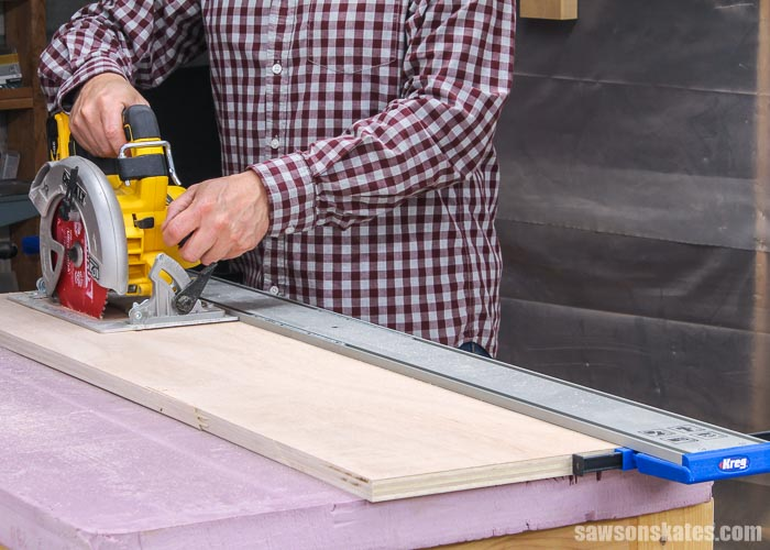 Using a circular saw with a Kreg Straight Edge Guide to cut a piece of plywood