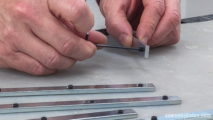 Using an Allen wrench to thread set screws into the connector bars of a Kreg Straight Edge Guide