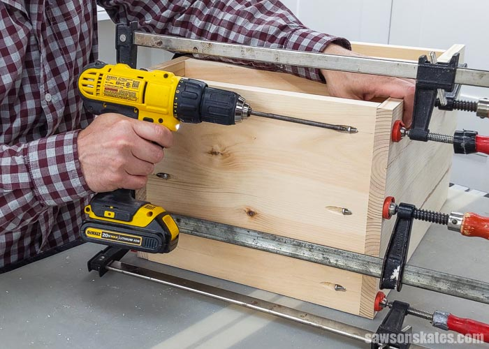 Using a drill to attach the top and bottom panel of a DIY sander cabinet