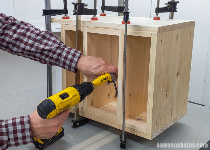 Using a right angle drill attachment to drive pocket screws inside of a