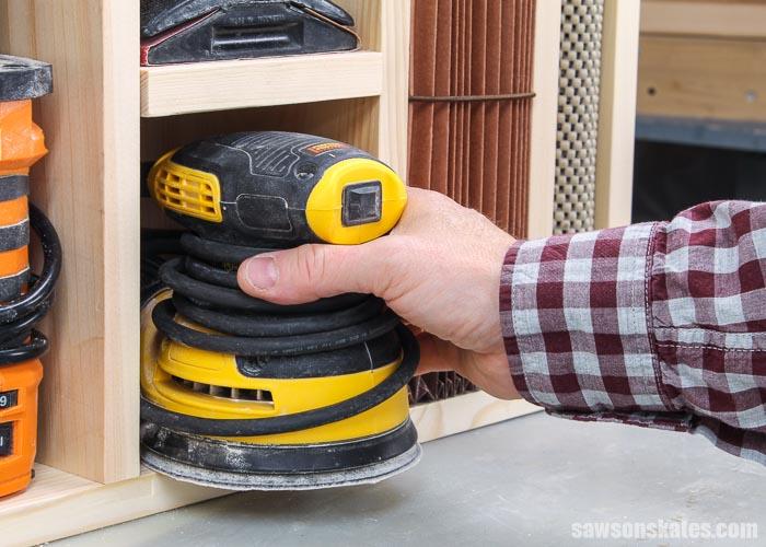 Hand removing a random orbit sander from a DIY sander organizer