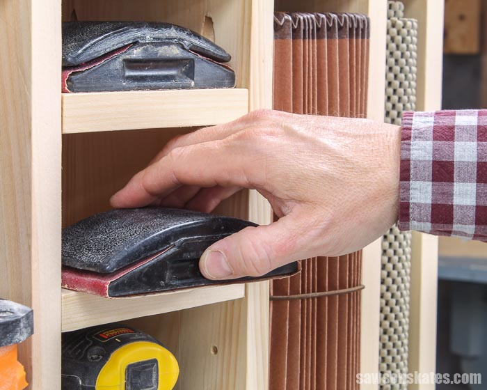 Hand removing a sanding block from a shelf of a DIY sander cabinet