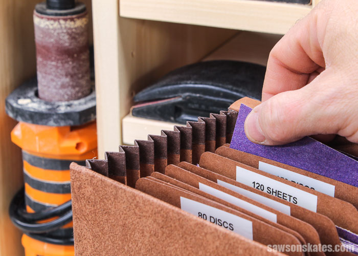 Hand removing a sheet of sandpaper from a DIY sander organizer
