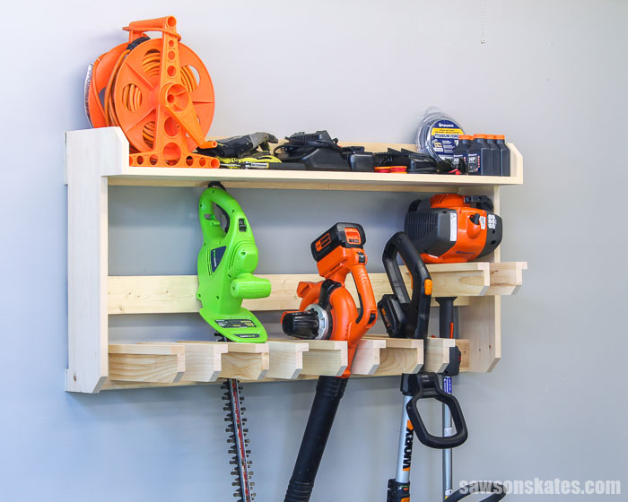 Get your garden tools organized with this DIY yard tool rack. This wall-mounted organizer is easy to customize for your tools and has a large storage shelf.