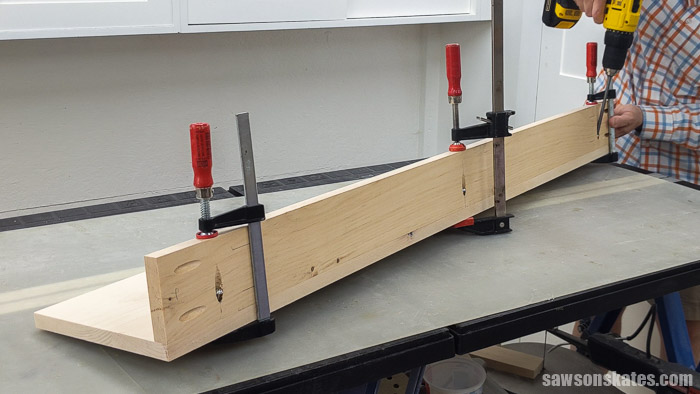 Using a drill to attach the back on a DIY lawn tool rack