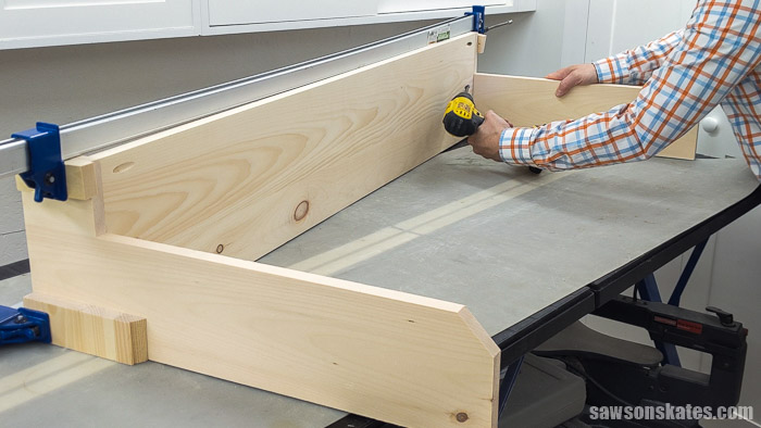 Using a drill to attach the side of a DIY garden tool rack