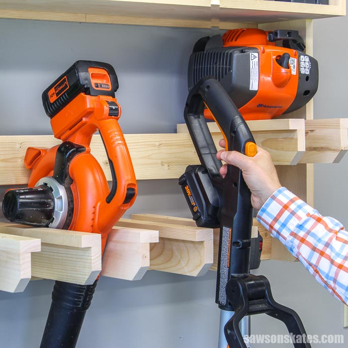 Hand removing a string trimmer from a wall-mounted DIY yard tool rack