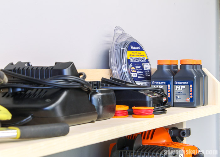 Shelf of a DIY yard tool rack filled with lawn tool supplies