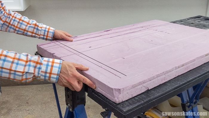 Placing a piece of foam insulation to cut a french cleat