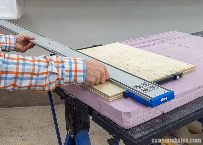 Position a straight edge guide on a piece of plywood to cut a french cleat