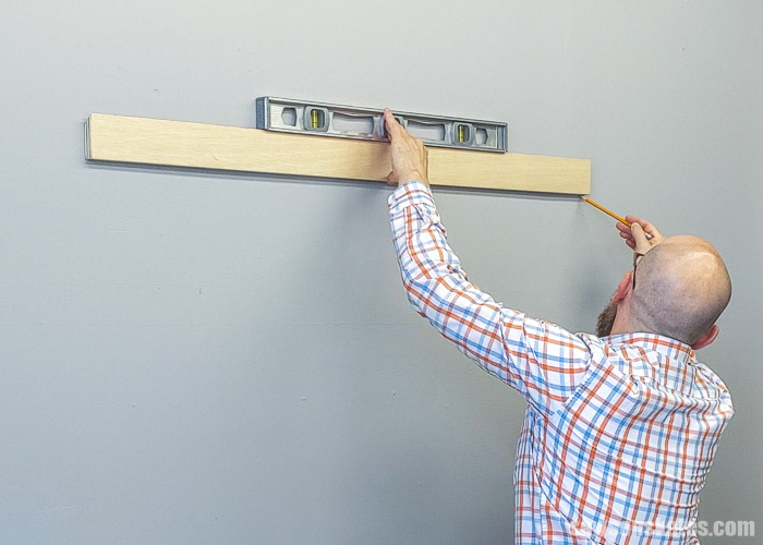 Using a pencil to mark the bottom of a DIY french cleat on the wall
