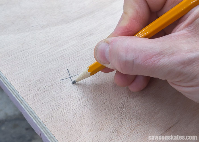Marking an x on the waste side before making a cut with a Kreg Straight Edge Guide