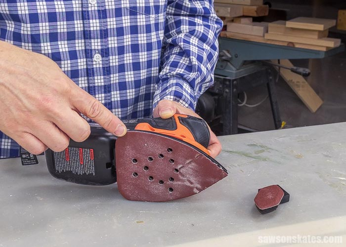Showing the triangular sandpaper pad on a detail sander