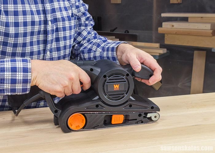 Using a belt sander to sand a table top