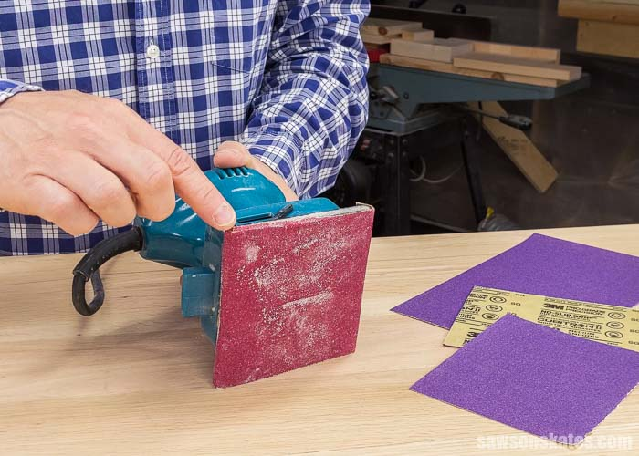 Pointing to the sanding pad on a palm sander