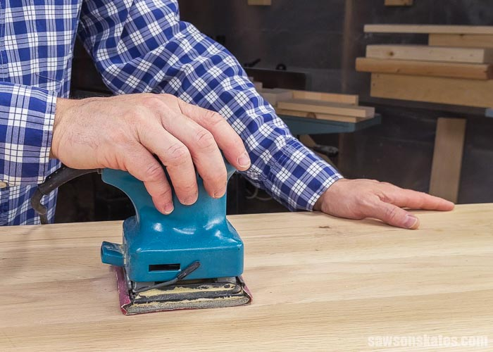 Using a palm sander to sand a table top