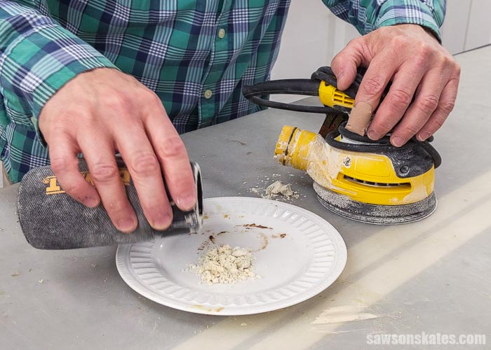 Pouring sanding dust on a plate to make a homemade stainable wood filler